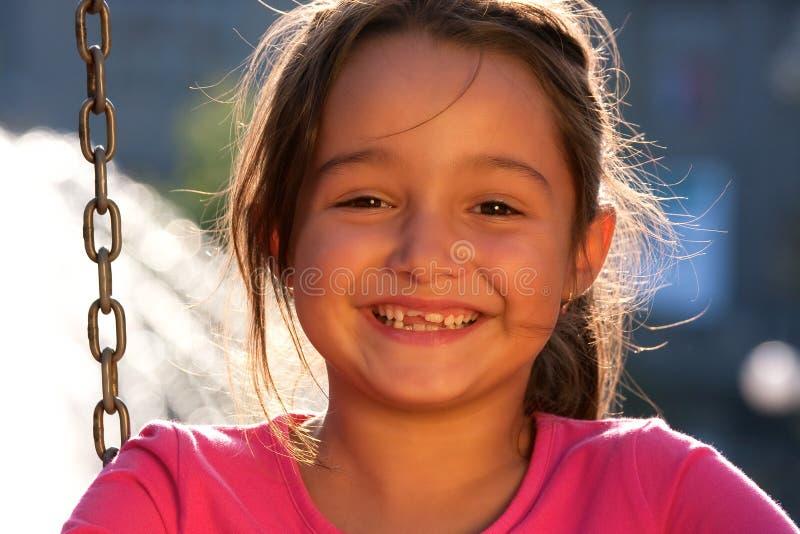 Smiling little girl on swing stock photography