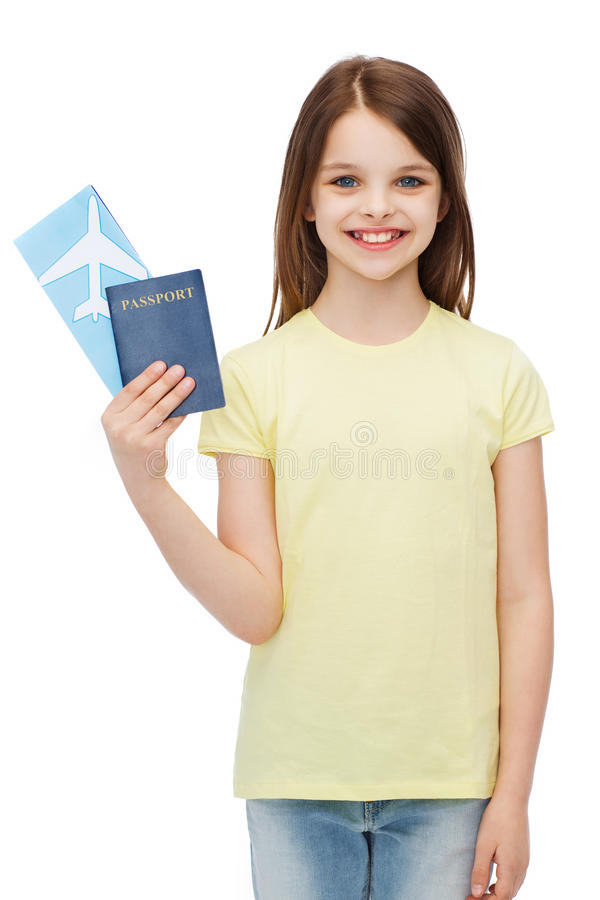 Smiling little girl with ticket and passport. Travel, holiday, vacation, childhood and transportation concept - smiling little girl with airplane ticket and stock photography