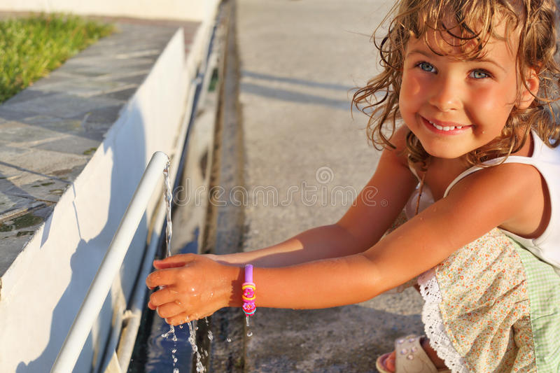 Smiling little girl washes hands water from pipe stock image