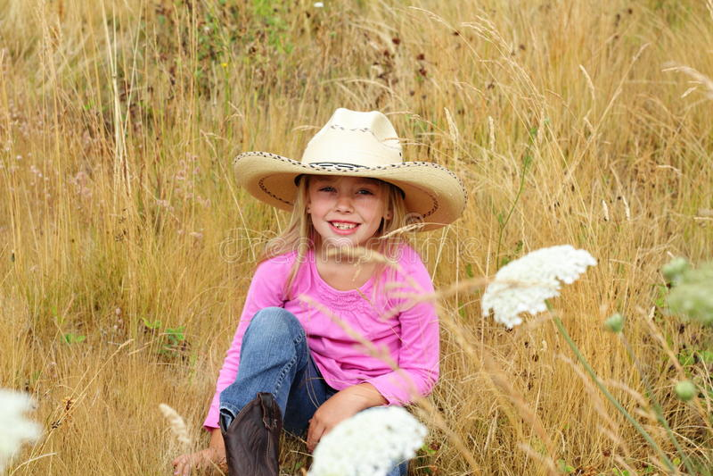 Smiling little girl wearing large hat.