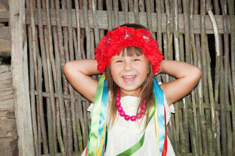 Smiling little girl in a wreath of red flowers and satin ribbons near the wicker fence royalty free stock images