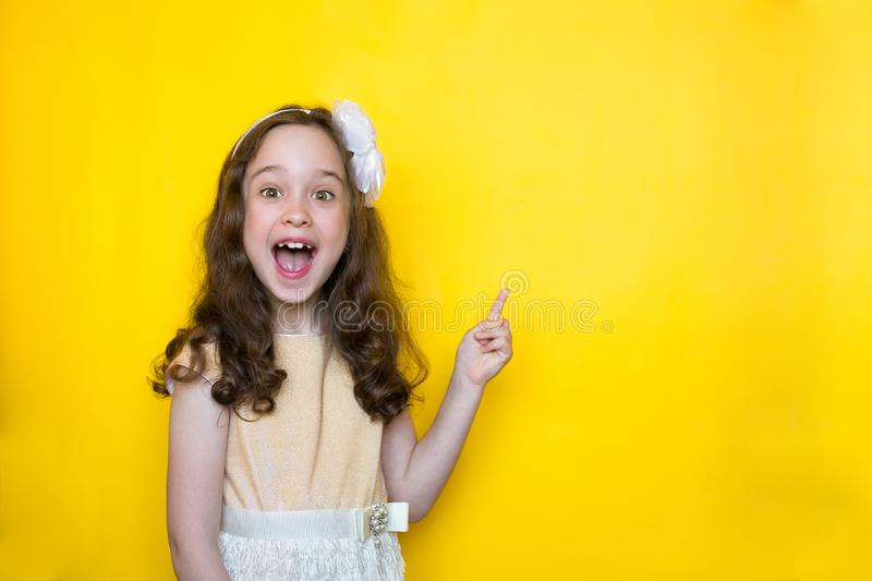 Smiling little girl on yellow background points her finger at the space for lettering. Concept of education stock photography