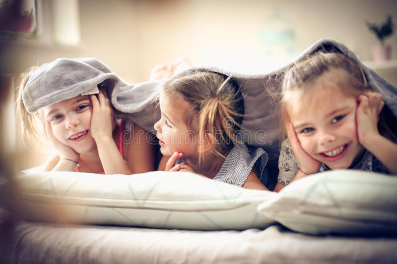 Smiling little girls in bed. Three little girls in bed covered over head. Space for copy stock images