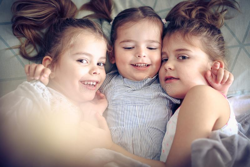 Smiling little girls. Three little girls lying in bed and hugging. Space for copy stock images
