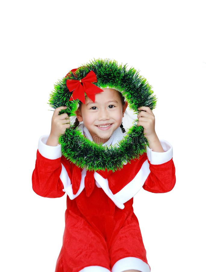 Smiling little kid girl in Santa costume dress with holding Christmas round wreath on her face on white background. Merry Christma. S and Happy New Year Concept royalty free stock image