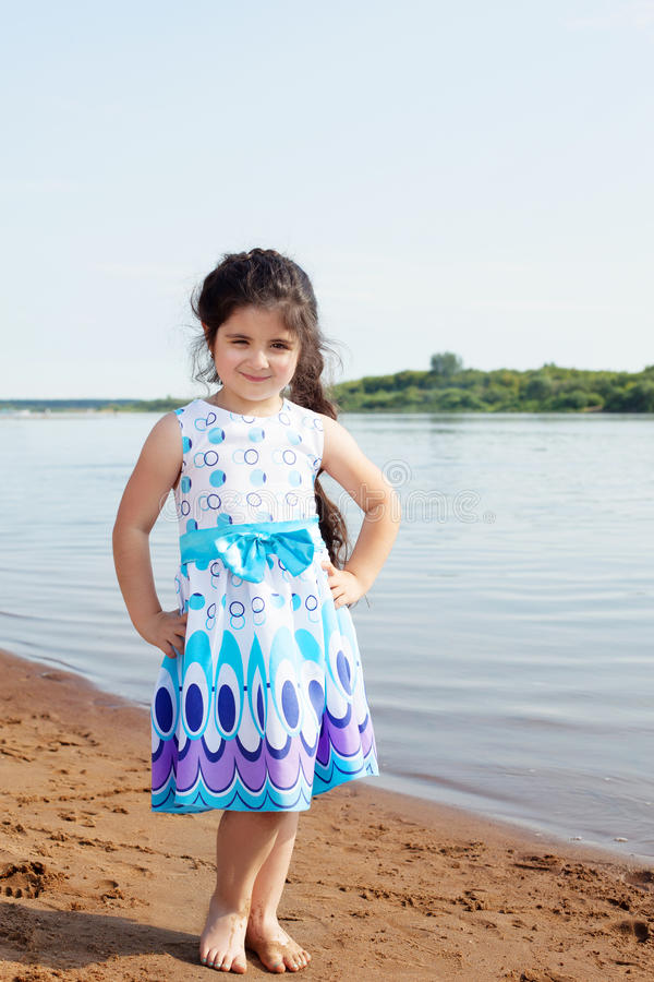 Smiling little model posing on river background. Image of smiling little model posing on river backdrop stock photo