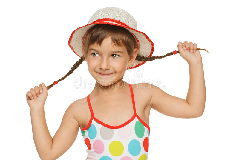 Smiling little playing with her braids. Little girl in swimming wear playing with her braids, over white background royalty free stock images