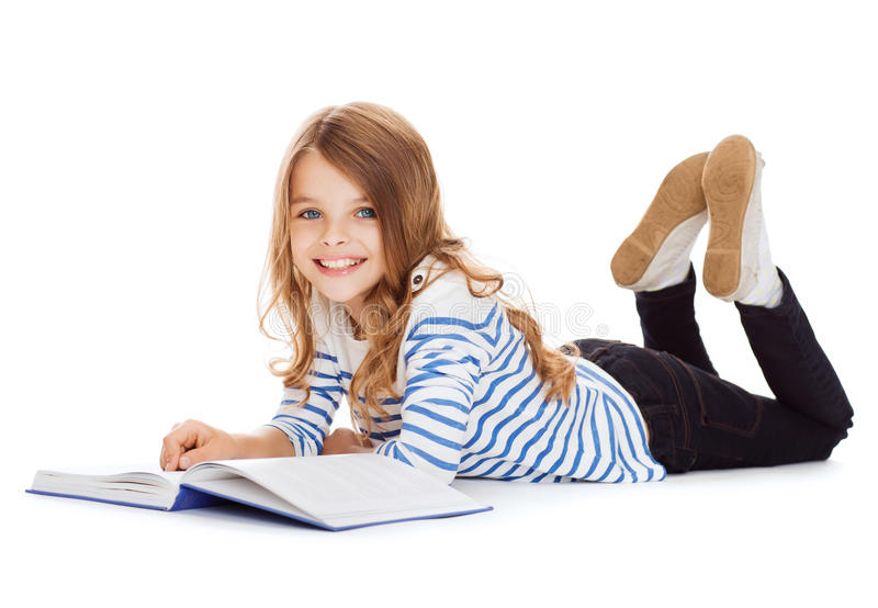 Smiling little student girl lying on the floor royalty free stock images