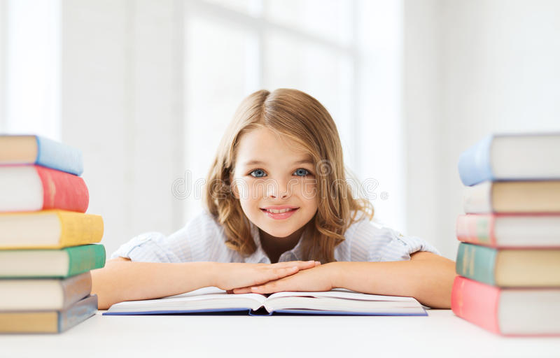 Smiling little student girl with many books stock photos