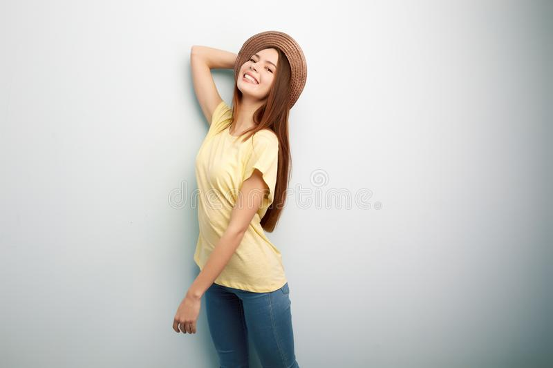 Smiling long haired girl dressed in a yellow t-shirt, jeans and hat stands on a white background in the studio royalty free stock photography