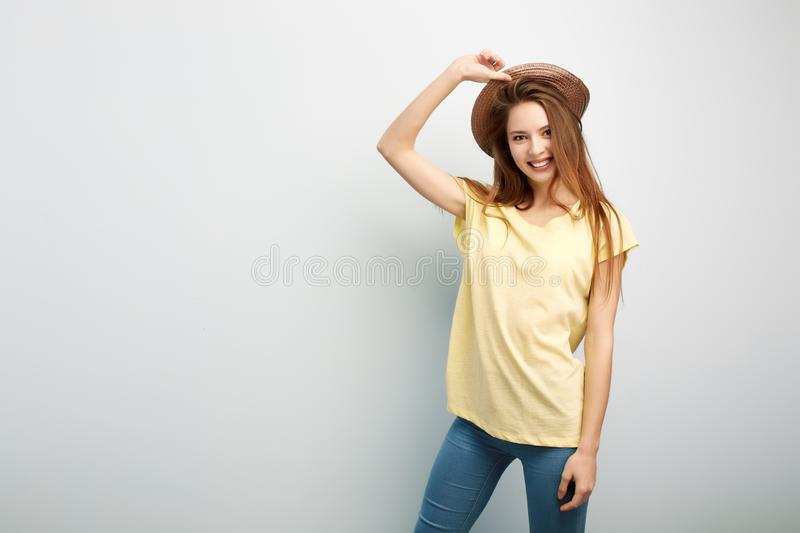 Smiling long haired girl dressed in a yellow t-shirt, jeans and hat stands on a white background in the studio royalty free stock images