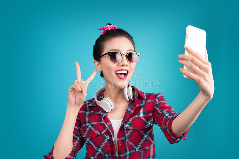 Smiling lovely active asian girl taking selfie photo. stock photo
