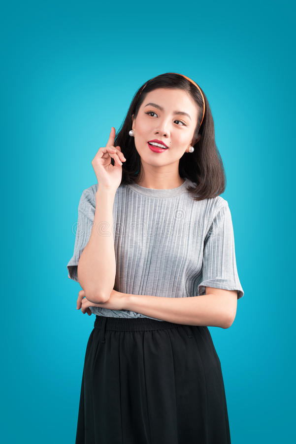 Smiling lovely asian woman dressed in pin-up style dress over bl. Ue stock photo