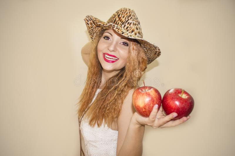 Smiling lovely woman holding two apples royalty free stock photography