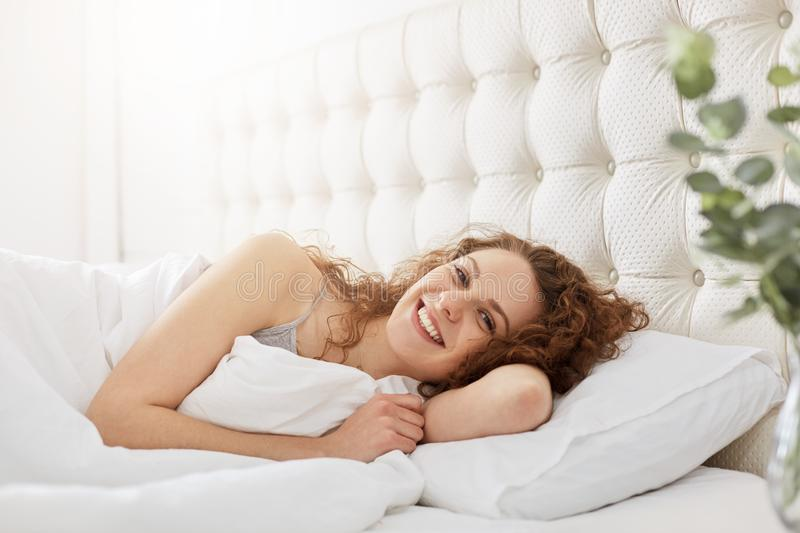 Smiling lovely young woman wakes up in morning, has gladful expression, lies on white bedclothes in bed, poses at camera with sati. Sfied expression. People stock image