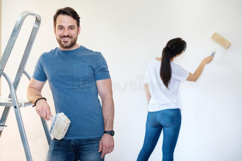 Happy couple painting walls in their new house ready for living royalty free stock images