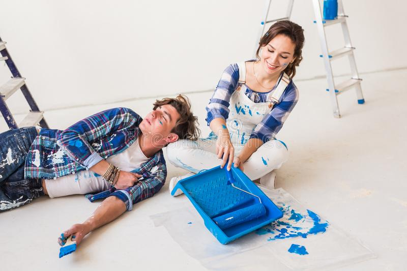 Smiling loving couple doing home renovations. Young woman is holding a paint roller and young man is resting stock image