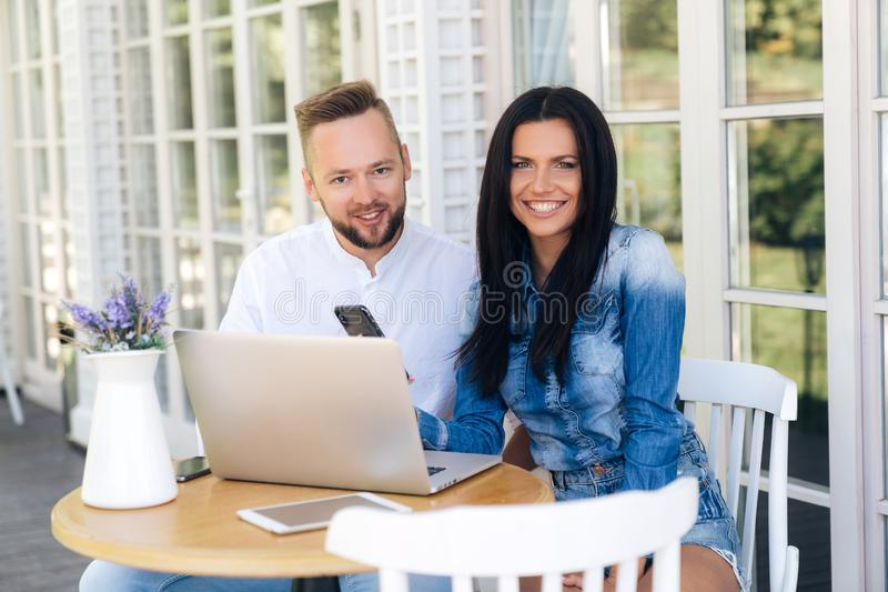 Smiling loving couple sitting at a table on a stool in a cafe. Young people in a good mood are shopping on the Internet royalty free stock photography
