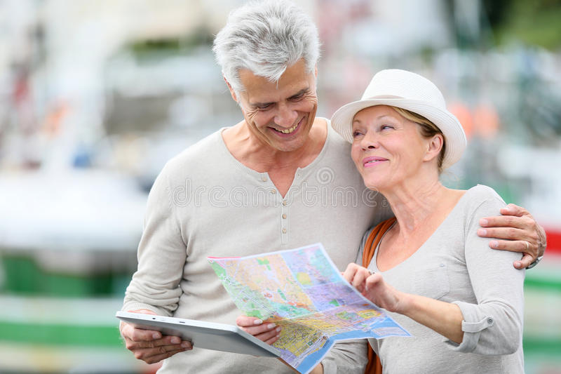 Smiling loving senior couple using map and tablet visiting royalty free stock images