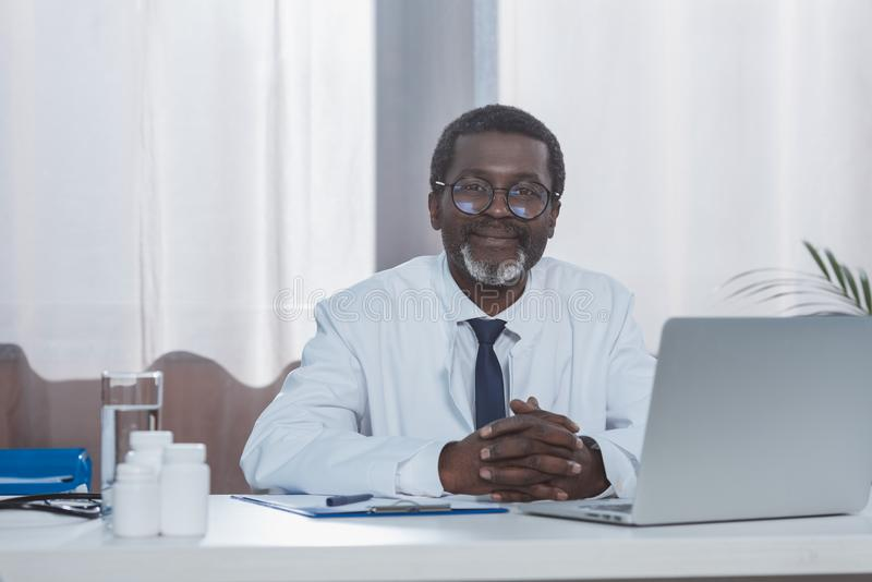 Smiling male african american doctor sitting at the table and looking royalty free stock image