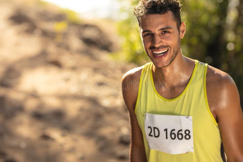 Smiling male athlete in mountain trail race royalty free stock image