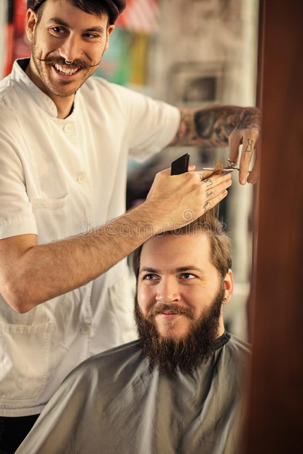 Smiling male barber giving client haircut royalty free stock photography