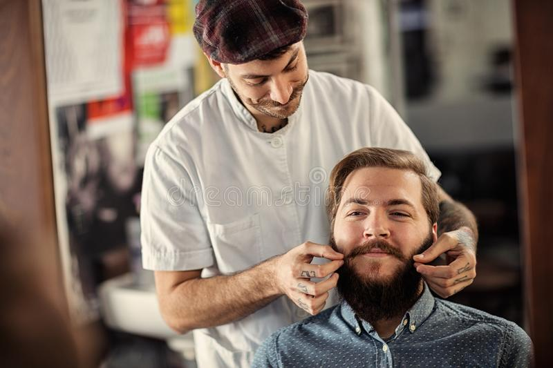 Smiling male barber is serving his client stock images