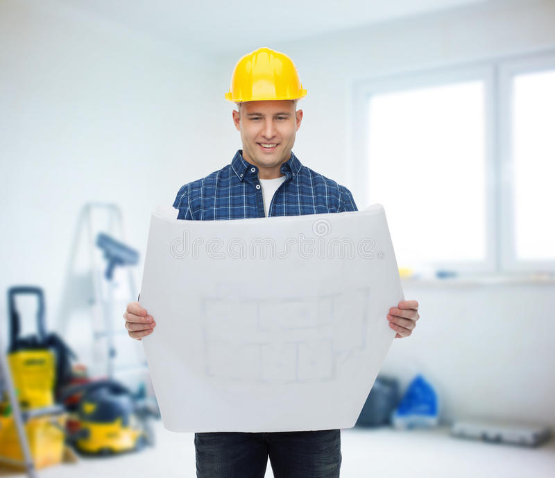 Smiling male builder in helmet with blueprint stock photo image of repair construction building people and maintenance concept smiling male builder or manual worker in helmet reading blueprint over room with work malvernweather Image collections
