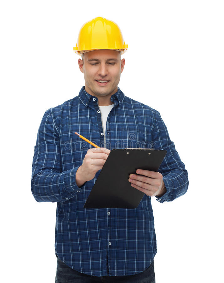 Smiling male builder in helmet with clipboard. Repair, construction, building, people and maintenance concept - smiling male builder or manual worker in helmet royalty free stock image