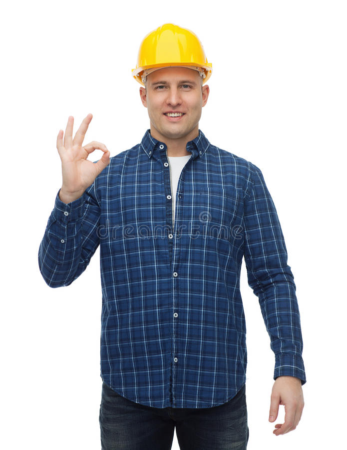 Smiling male builder in helmet showing ok sign stock photos
