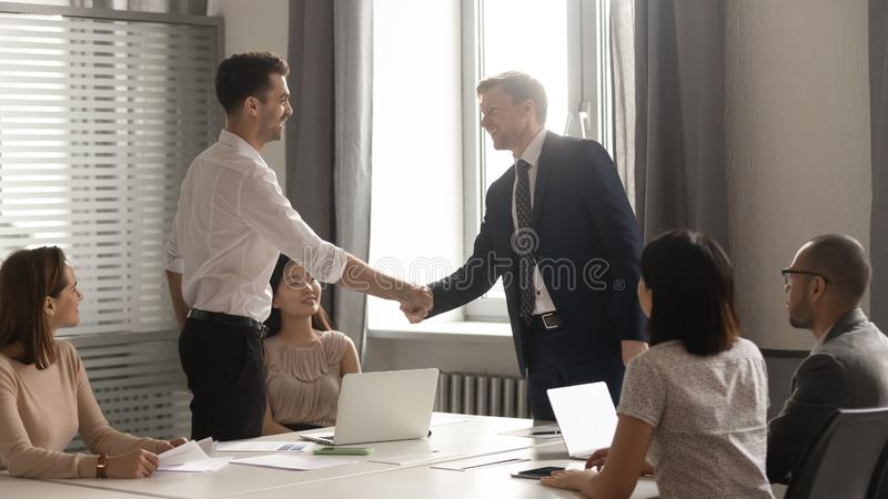 Male business partners negotiators handshake at group office meeting negotiations royalty free stock photos