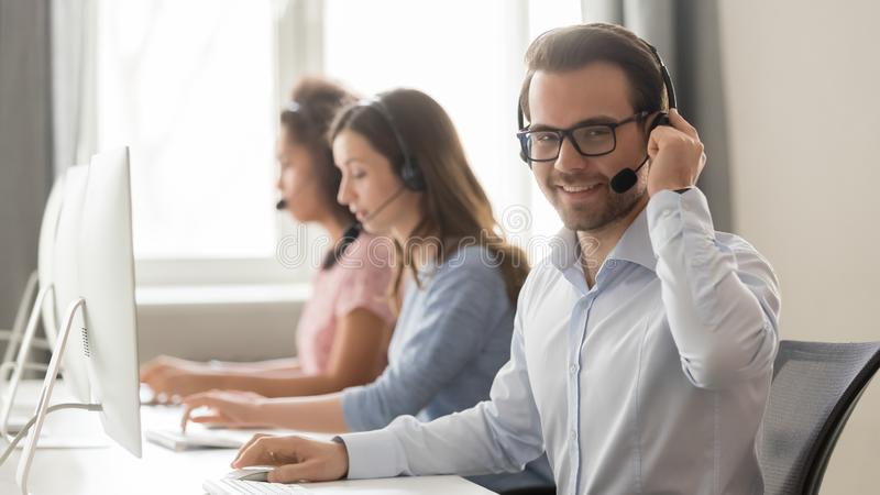 Smiling male call center operator in headset looking at camera stock photography
