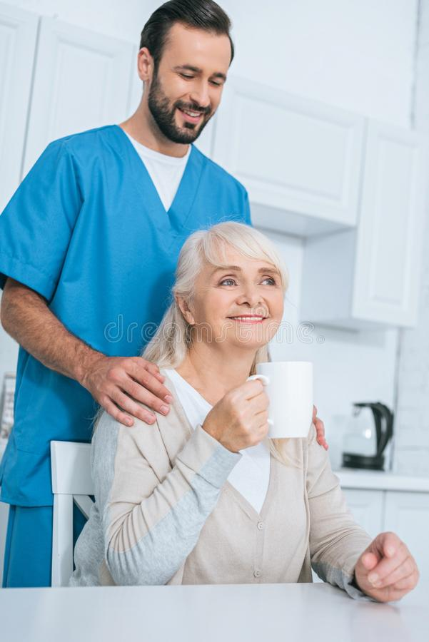 Smiling male caregiver looking at senior woman. Drinking tea in kitchen stock images