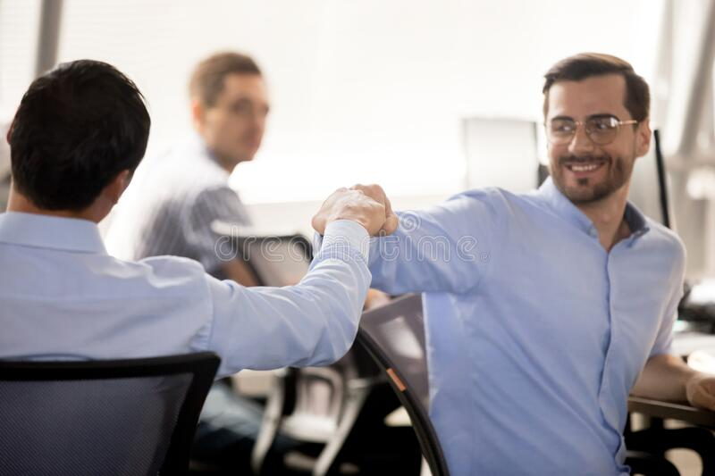 Smiling employees give fists bump greeting at workplace stock images