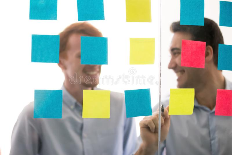 Smiling male colleagues present project on sticky notes. Smiling male colleagues work on project present ideas on post-it sticky notes on office glass wall royalty free stock photos