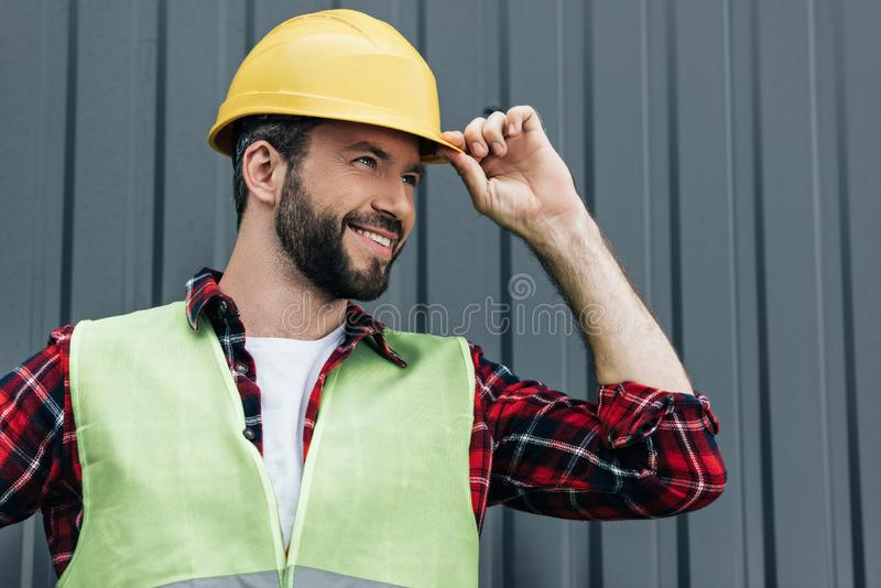 smiling male constructor in safety vest and helmet standing royalty free stock photos