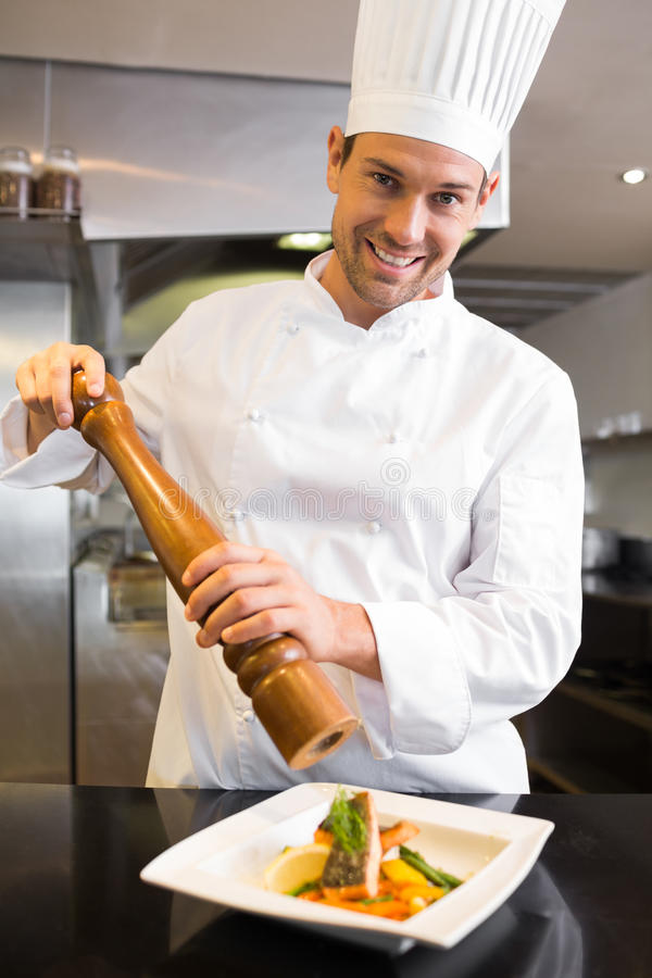 Smiling male cook grinding pepper on food in kitchen. Portrait of a smiling male cook grinding pepper on food in the kitchen royalty free stock photo