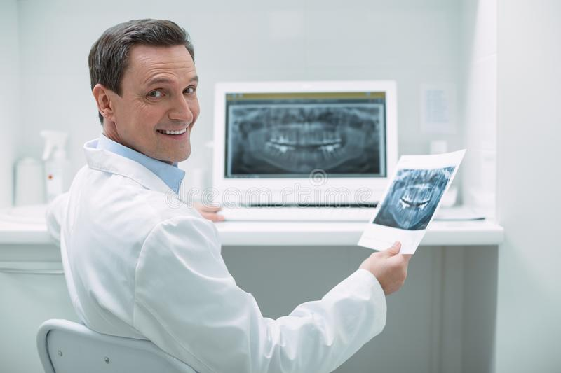 Smiling male dentist holding an image stock images