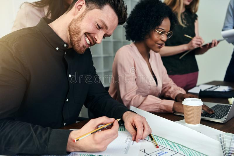 Smiling male designer and collegues working together in an office royalty free stock photo