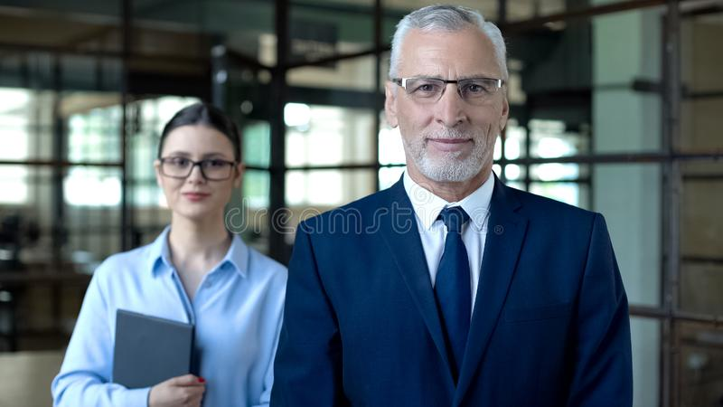 Smiling male director and female secretary looking camera, office work, business stock photos