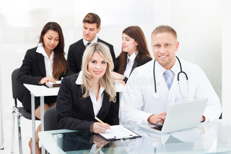 Smiling male doctor and businesswoman with laptop stock photo