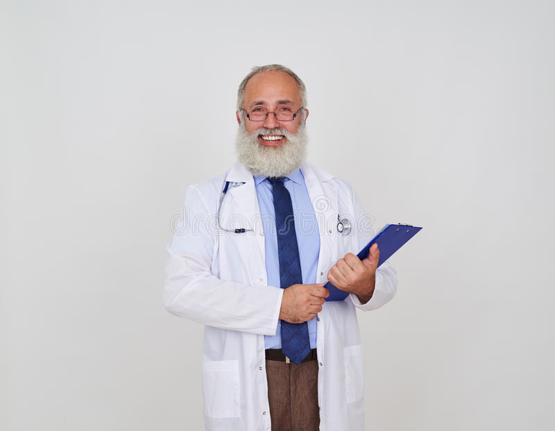 Smiling male doctor with a folder in uniform standing against white background stock photography