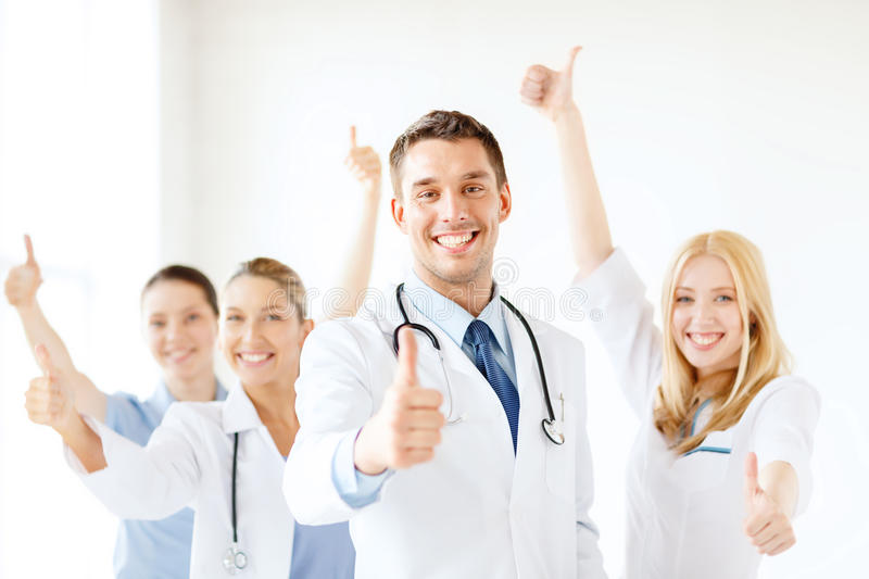 Smiling male doctor in front of medical group. Healthcare and medicine concept - attractive male doctor in front of medical group in hospital showing thumbs up stock images