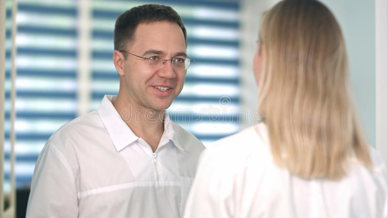 Smiling male doctor in glasses talking to female nurse stock photography