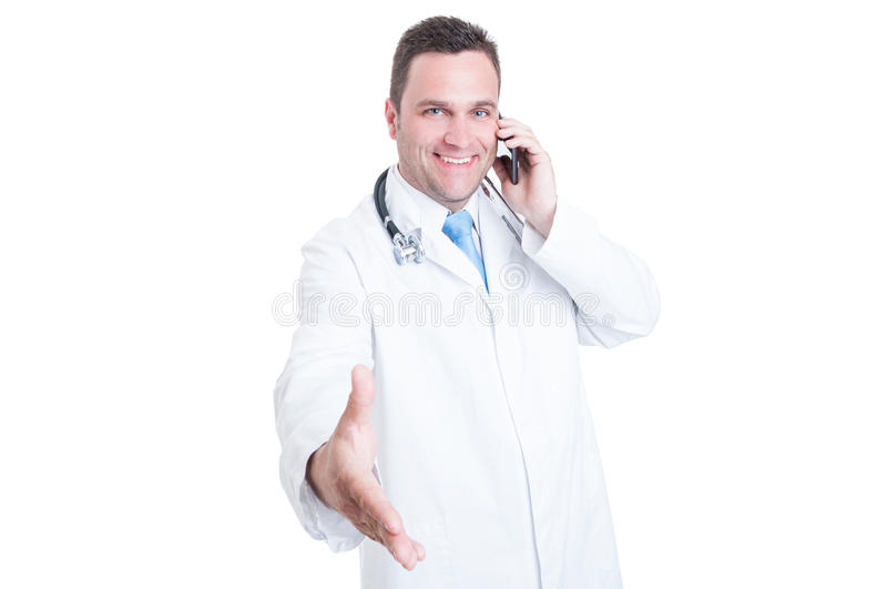 Smiling male doctor offering a handshake and speaking at phone. Smiling male doctor or medic smiling offering a handshake and speaking at phone isolated on white stock images