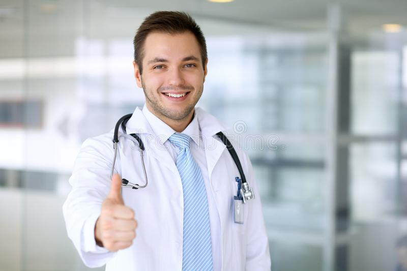 Smiling male doctor with thumb up stock image