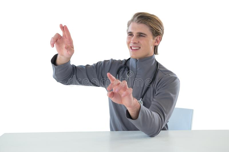 Smiling male doctor touching imaginary interface screen while sitting at table. Against white background stock photos