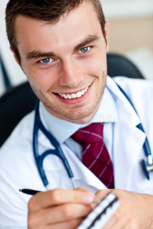 Smiling male doctor writing a perscription