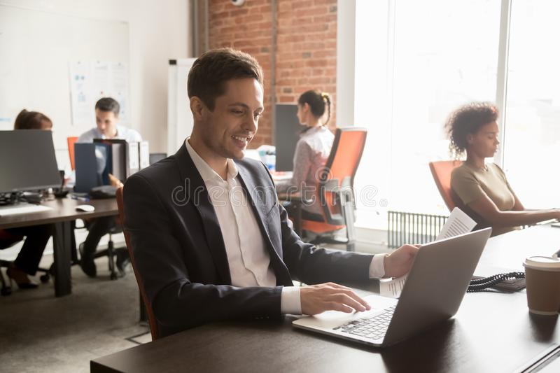 Smiling male employee work with document on laptop stock photos