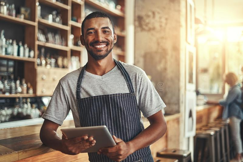 Smiling male entrepreneur in his coffee shop holding digital tab. Startup successful male entrepreneur standing in his coffee shop at the counter holding digital royalty free stock images